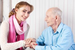 elderly man holding his caretaker's hands
